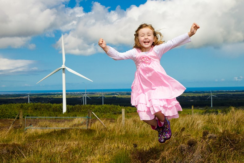 Child playing near wind farm